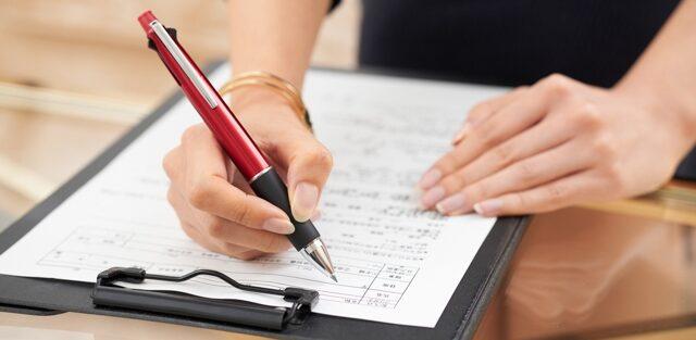 探偵社の調査依頼契約書に署名している依頼者
