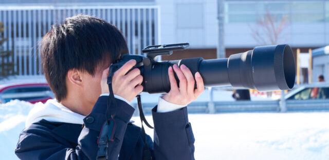 望遠レンズで浮気の決定的瞬間を撮影している探偵